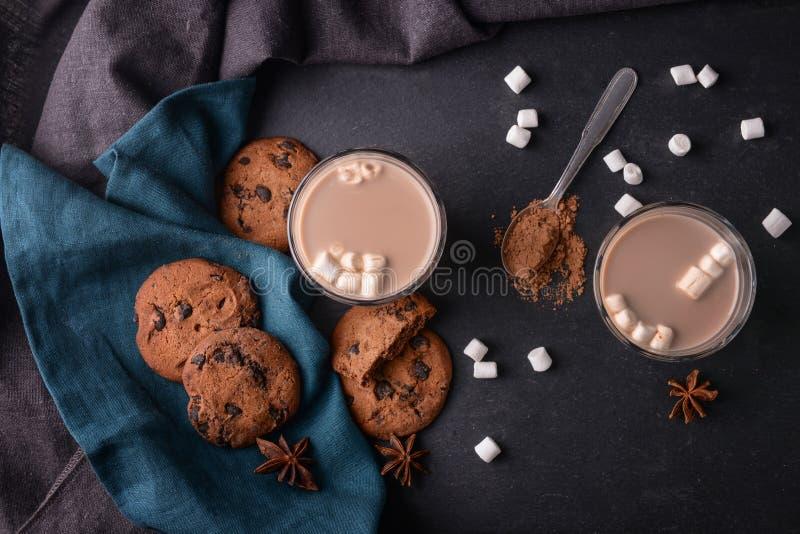 Vidrios de la bebida deliciosa del cacao con las melcochas y las galletas en la tabla fotografía de archivo libre de regalías