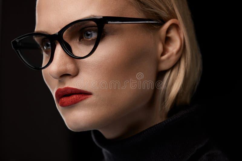 Vidrios de la moda de la mujer que llevan Hembra con los labios rojos en gafas imagenes de archivo