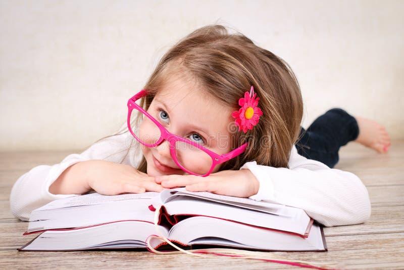 Vidrios de la muchacha preescolar y libros de lectura que llevan fotos de archivo