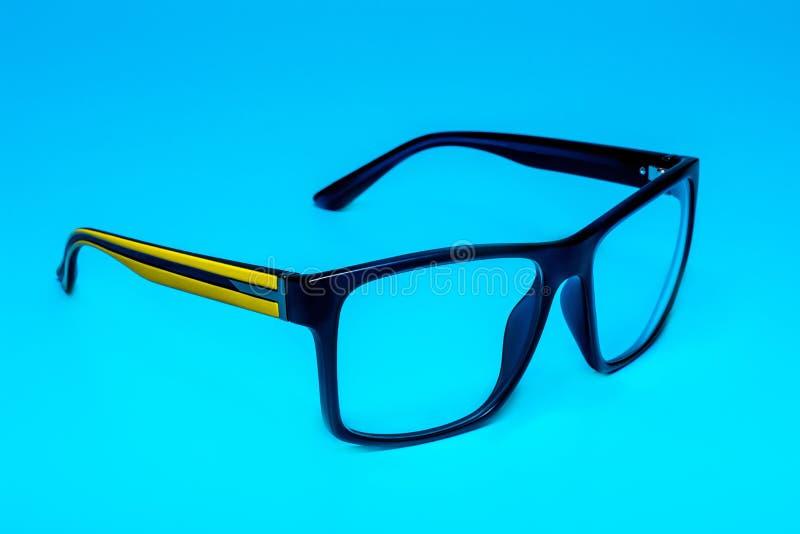 Vidrios de la protección ocular del ordenador con un cierre amarillo del grillo para arriba en un fondo azul, aislamiento imagen de archivo libre de regalías