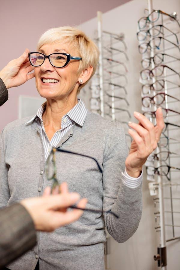 Vidrios de lectura de compra de la mujer mayor en tienda óptica fotos de archivo