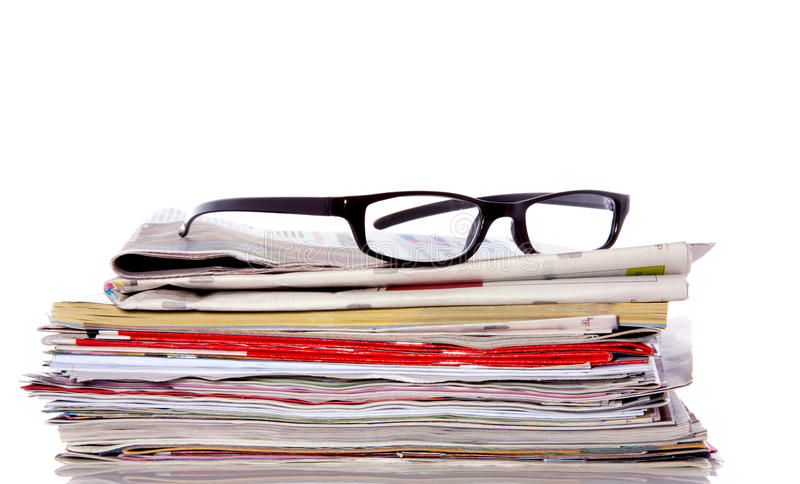 Vidrios de lectura en el periódico fotos de archivo
