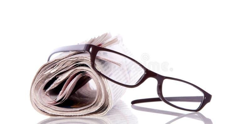 Vidrios de lectura en el periódico imagenes de archivo