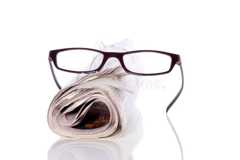 Vidrios de lectura en el periódico imagen de archivo libre de regalías