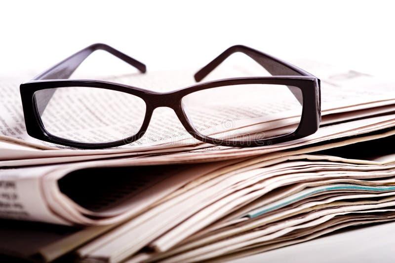 Vidrios de lectura en los periódicos imagen de archivo