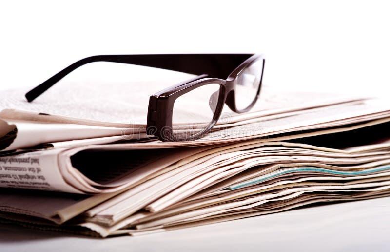 Vidrios de lectura en los periódicos fotografía de archivo