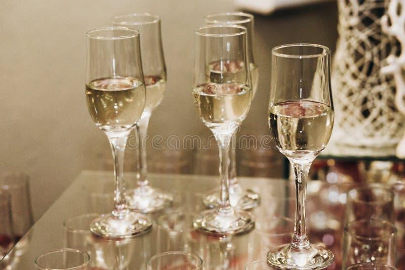 Vidrios de lujo del champán en la tabla en el primer del restaurante, elegan imagen de archivo
