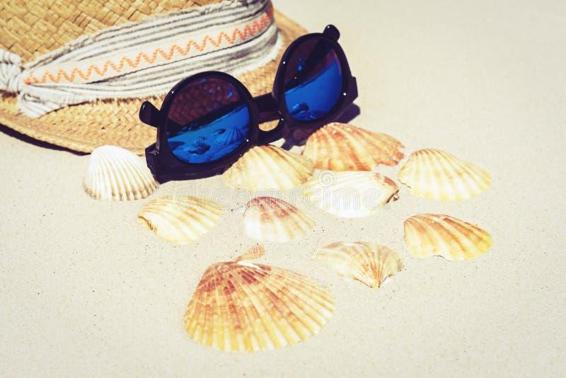 Vidrios de mimbre del sombrero y de sol de la playa de la paja del verano del vintage en la arena con las conchas marinas, fondo  foto de archivo