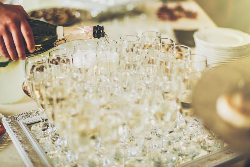 Vidrios de oro de Champán champán de colada del camarero en gl elegante fotografía de archivo libre de regalías