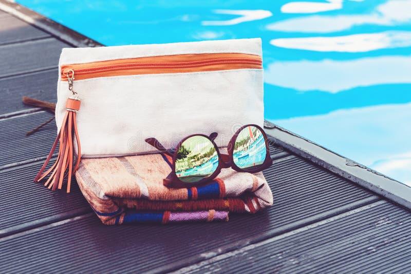 Vidrios de Sun, bolso cosmético, abrigo de la ropa de playa del encubrimiento cerca de la piscina, fondo tropical foto de archivo libre de regalías