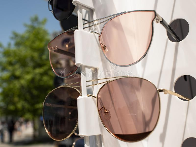 Vidrios de Sun en el contador dos pares de gafas de sol en diversos colores imagen de archivo libre de regalías