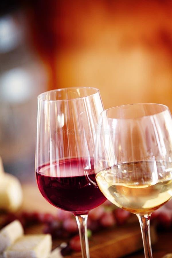 Vidrios de vino blanco rojo y en una tabla fotografía de archivo libre de regalías