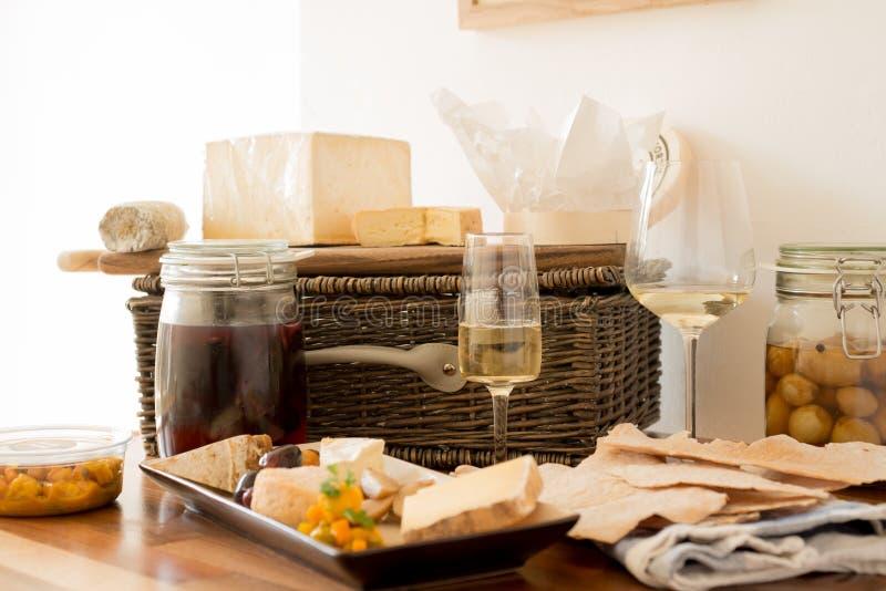 Vidrios de vino con las porciones del queso y de las galletas imágenes de archivo libres de regalías