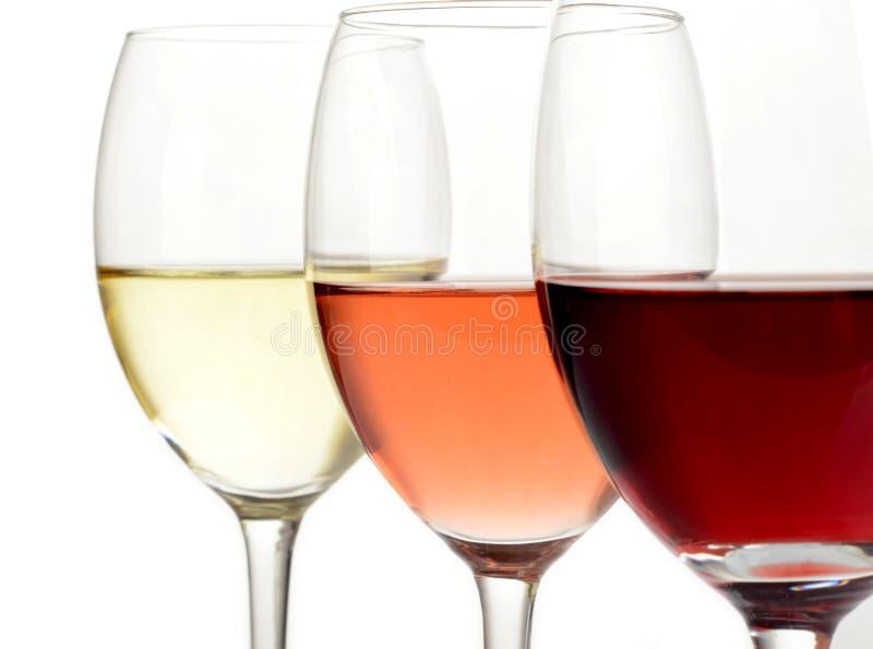 Vidrios de vino del blanco, color de rosa y rojo imagen de archivo