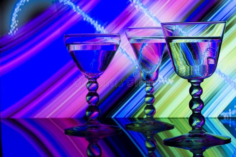 Vidrios de vino en fondo rayado del neón   imágenes de archivo libres de regalías