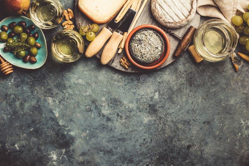 Vidrios de vino espumoso blanco con queso, uvas, nueces, oliv imagen de archivo libre de regalías