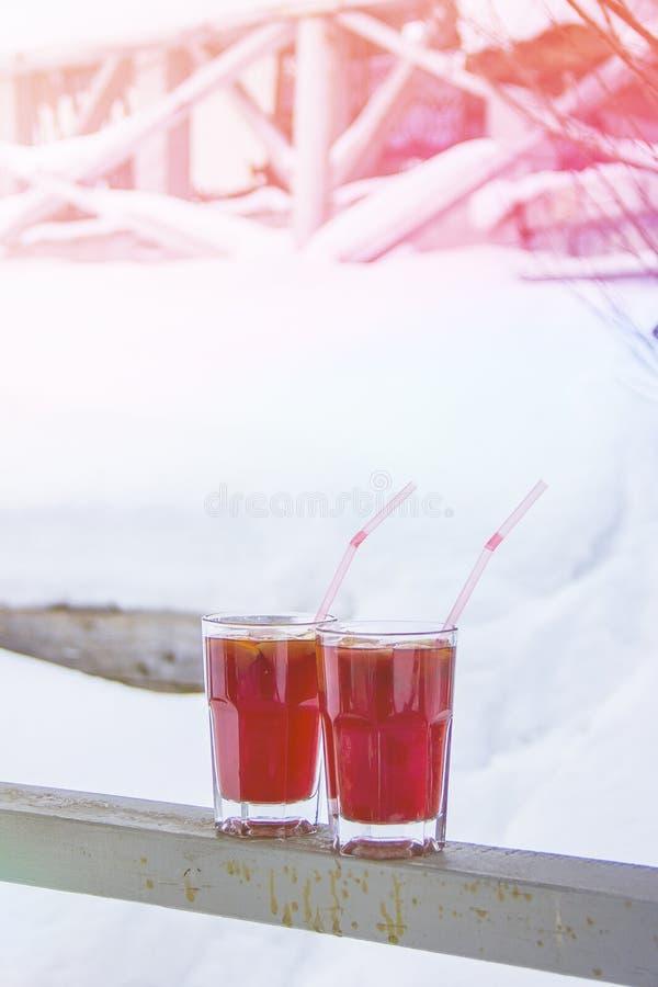 Vidrios de vino reflexionado sobre en nieve Vino caliente en un vidrio Mañana en las montañas foto de archivo