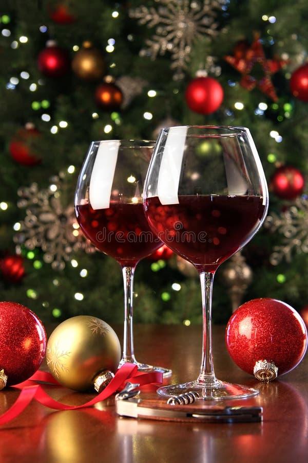 Vidrios de vino rojo delante del árbol de navidad fotografía de archivo libre de regalías