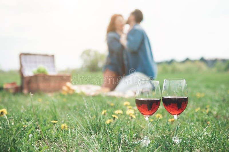 Vidrios de vino rojo en hierba cerca de pares cariñosos fotografía de archivo