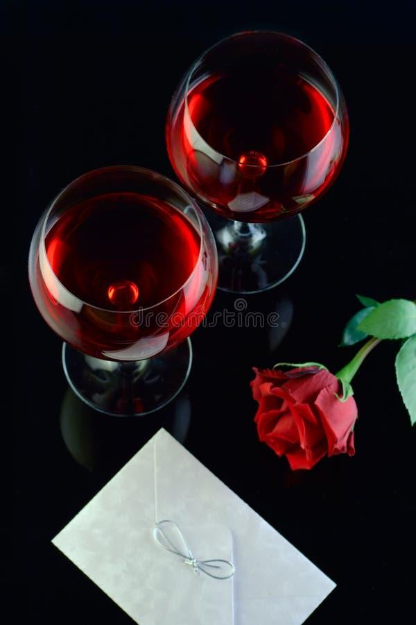 Vidrios de vino, rosa y una carta imagen de archivo