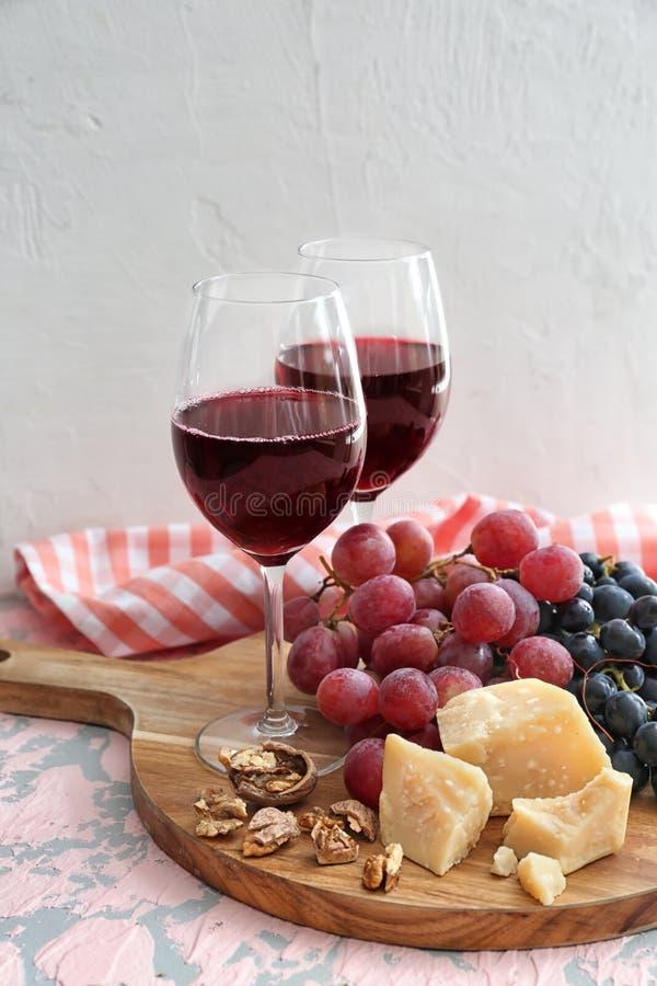 Vidrios de vino tinto con queso y uvas maduras en la tabla foto de archivo libre de regalías