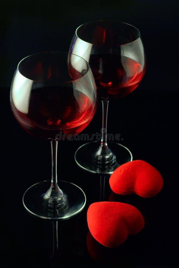 Vidrios de vino y dos corazones fotografía de archivo
