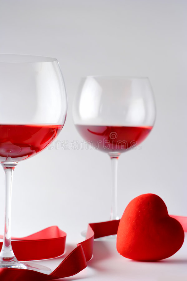 Vidrios de vino y un corazón fotos de archivo