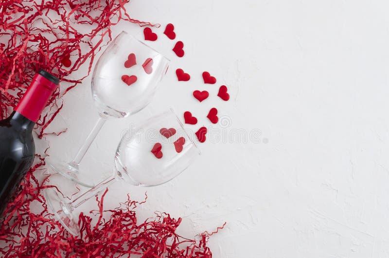 Vidrios del concepto y botella rom?nticos puestos planos de vino tinto en el fondo blanco con los corazones y la paja que embala  fotos de archivo libres de regalías