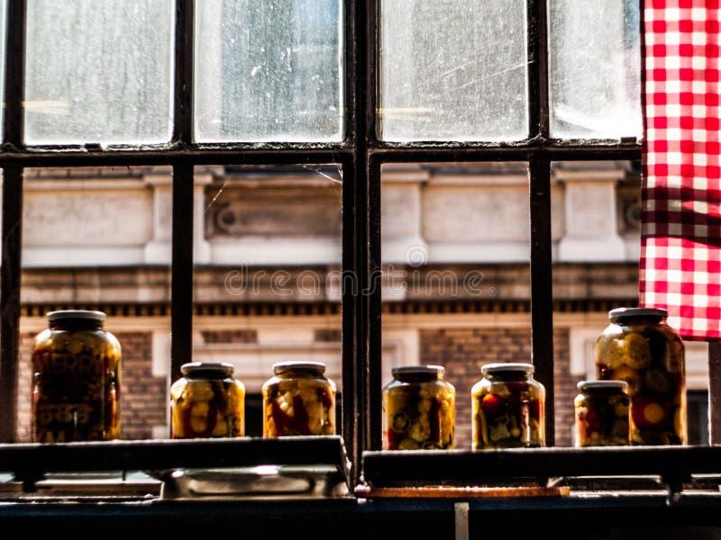 Vidrios del envase llenados de las verduras en una ventana iluminada por el sol durante la tarde en Budapest, Hungría fotos de archivo libres de regalías