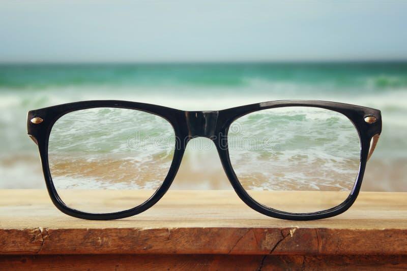 Vidrios del inconformista en una tabla rústica de madera delante del fondo del mar Vintage filtrado fotos de archivo libres de regalías