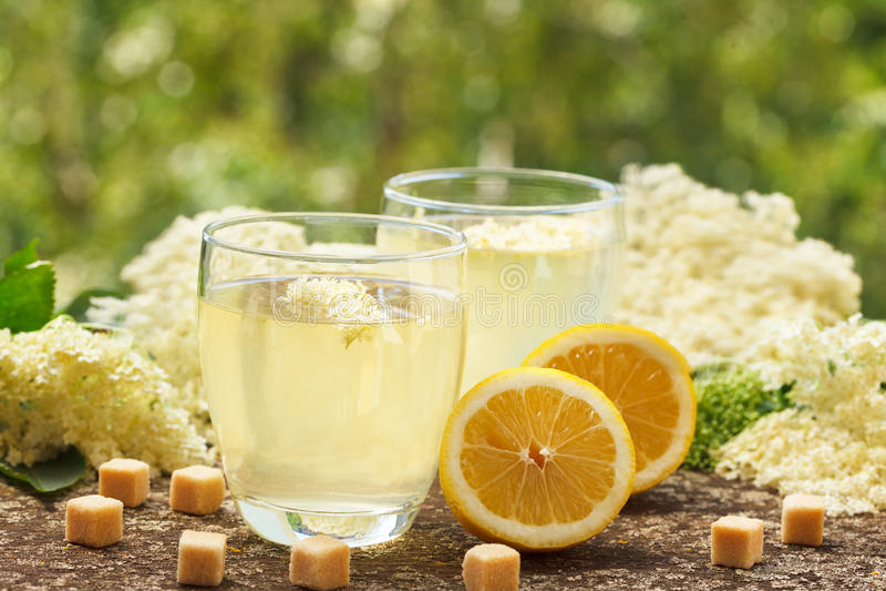 Vidrios del jugo, de las flores de la baya del saúco y del limón sanos imagenes de archivo