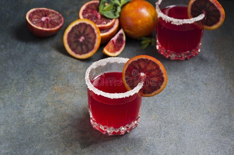 Vidrios del margarita de la naranja de sangre con el borde salado y rebanadas de fruta en la tabla rústica gris imagen de archivo