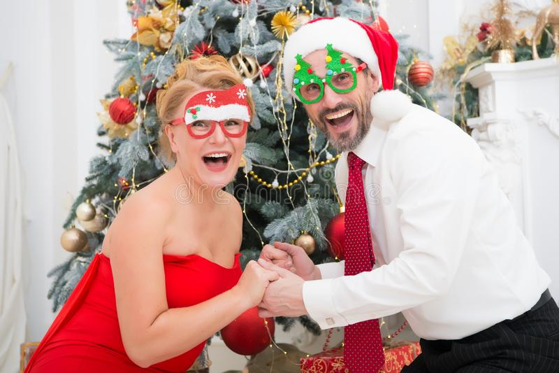 Vidrios del partido de los pares que llevan elegantes alegres y sorpresa de la expresión con el árbol de navidad en fondo fotografía de archivo