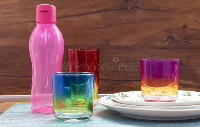 Vidrios del vidrio multicolor y de una botella rosada para las bebidas frías fotografía de archivo