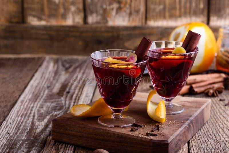 Vidrios del vino reflexionado sobre, bebida festiva de la fiesta de Navidad en la tabla rústica de madera imagen de archivo