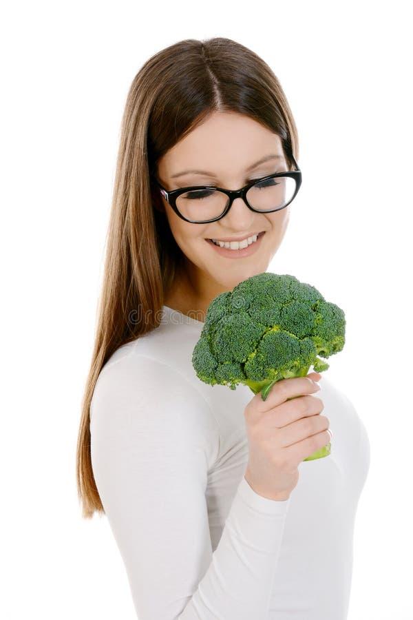 Vidrios del womanwearin y bróculi jovenes el sostenerse foto de archivo