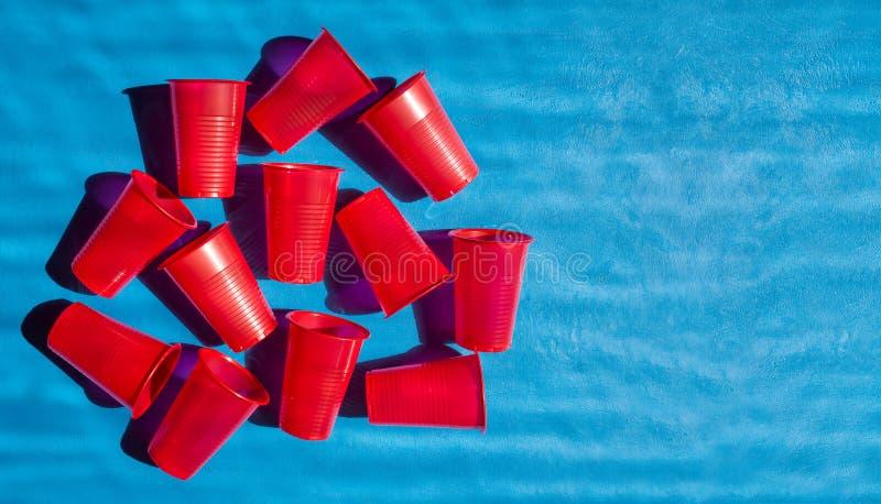Vidrios disponibles del plástico En las tazas rojas el sol brillante brilla creando una sombra Reciclaje y disposición de fotos de archivo libres de regalías