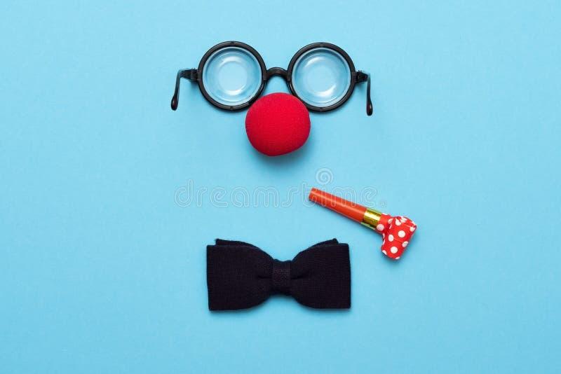 Vidrios divertidos, nariz roja del payaso y mentira del lazo en un fondo coloreado, como una cara foto de archivo