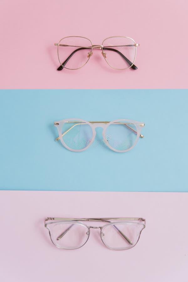 Vidrios elegantes de la imagen en un fondo en colores pastel Tres pares de vidrios con las lentes en un rosa y fondos azules eleg foto de archivo