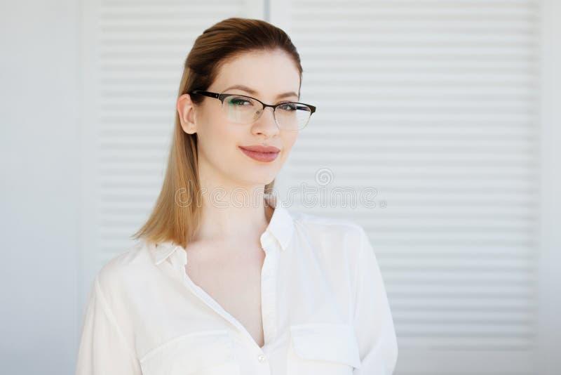 Vidrios elegantes en un marco fino, correcci?n de la visi?n Retrato de una mujer joven imagen de archivo