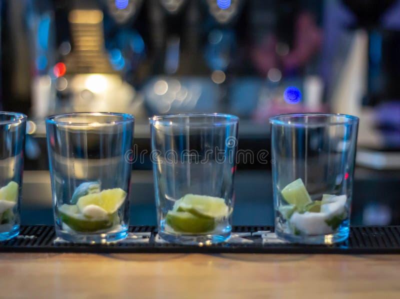 Vidrios en fila con las cuñas de limón en él listo para ser llenado de las diversas bebidas las barras locales, restaurantes tien fotos de archivo