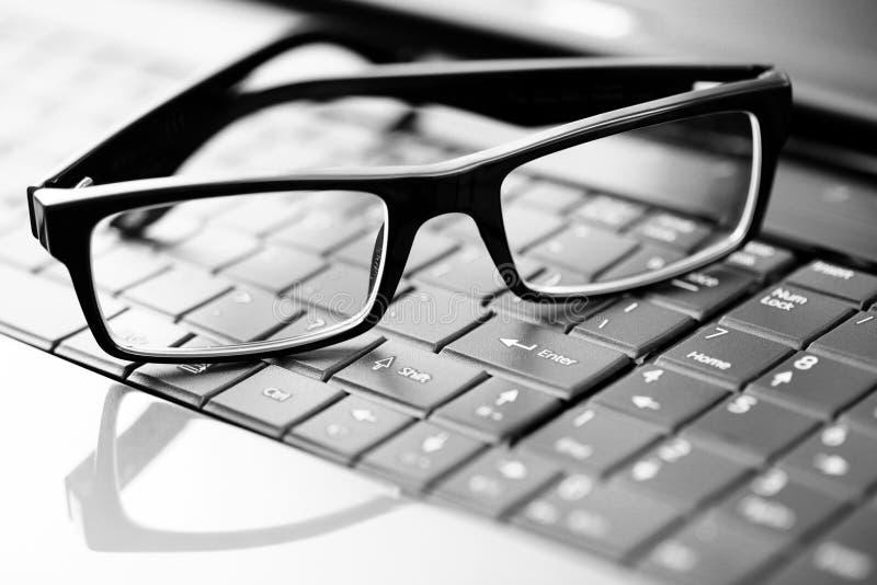 Vidrios en la computadora portátil fotografía de archivo libre de regalías