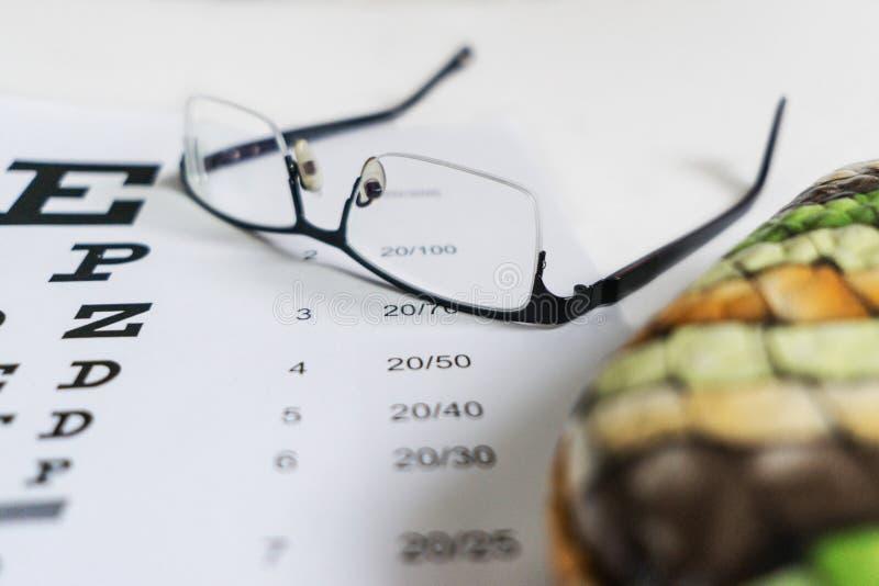 Vidrios en las manos en el fondo de la tabla para la visión imagenes de archivo