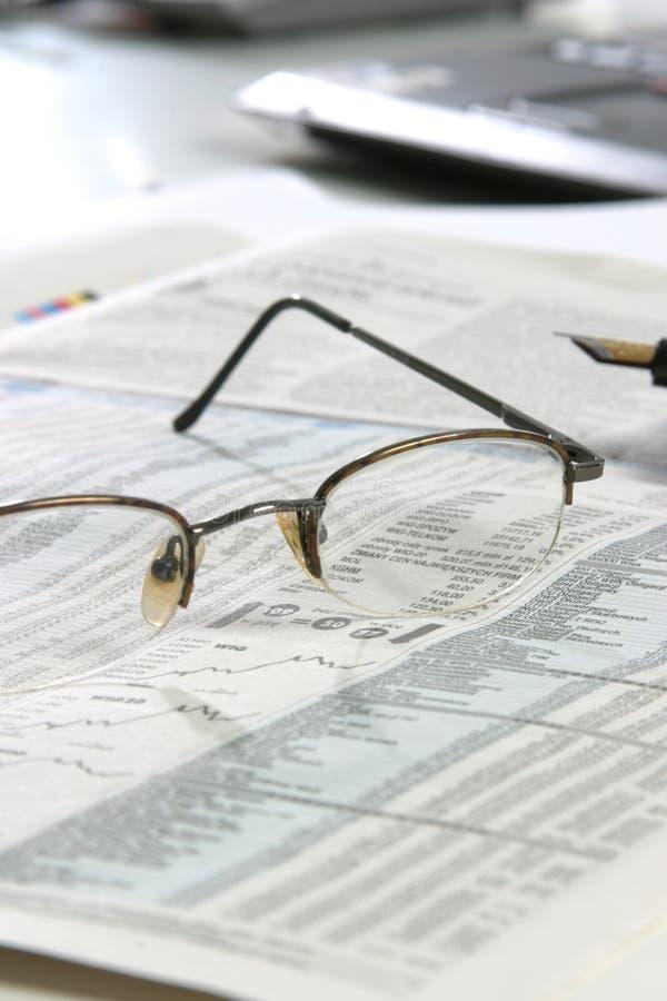 Vidrios en un newspapper imagen de archivo