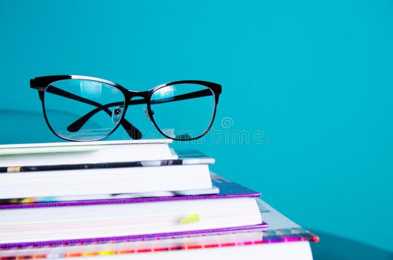 Vidrios en una pila de libros en el interior en un estilo minimalista Monocolor El concepto de lectura, educación, compra reserva fotos de archivo