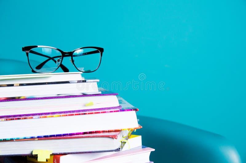 Vidrios en una pila de libros en el interior en un estilo minimalista Monocolor El concepto de lectura, educación, compra reserva fotos de archivo libres de regalías