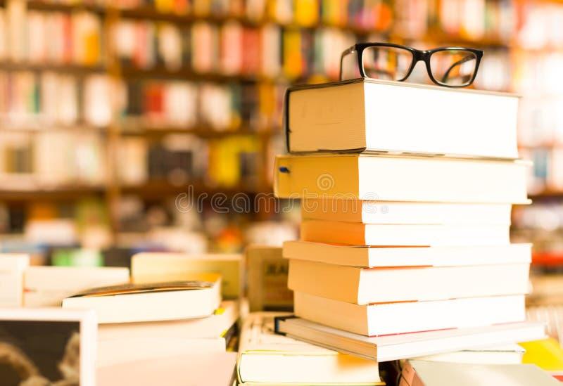 Vidrios encima de la pila de libros que mienten en la tabla en librería imagen de archivo libre de regalías