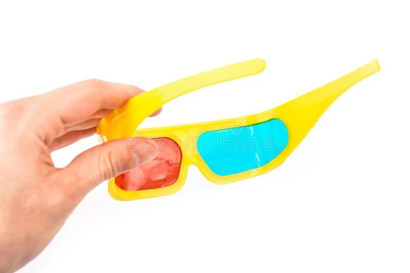 Vidrios estéreos amarillos en la mano en un fondo blanco imagen de archivo libre de regalías