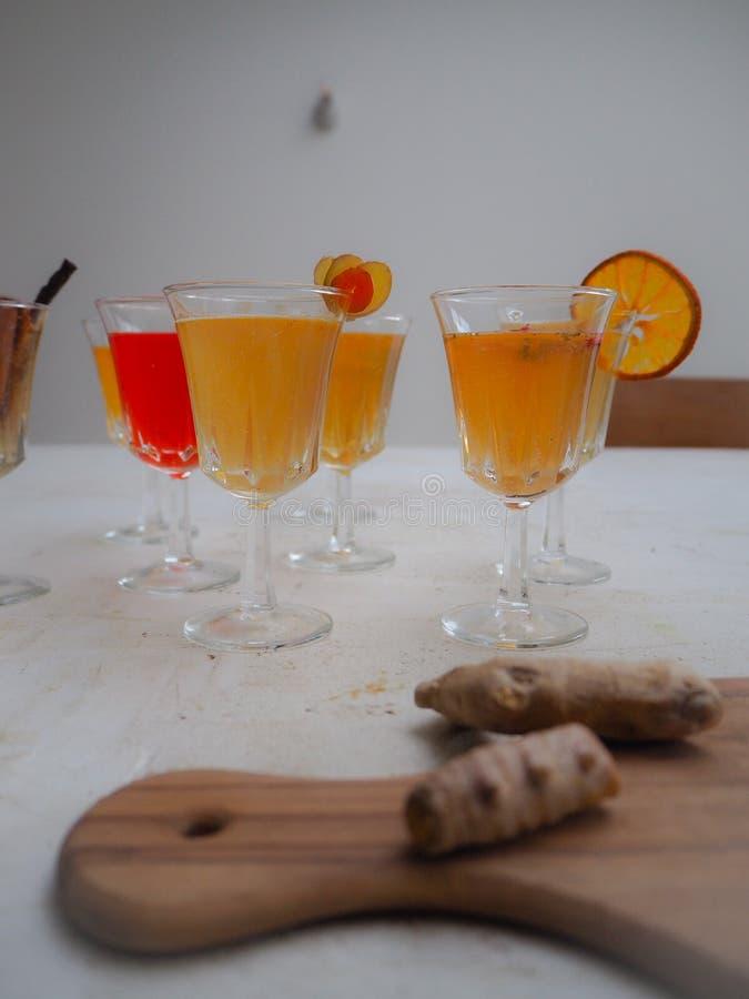 Vidrios múltiples con una variedad de té condimentado del kombucha y una tabla de cortar de madera con la cúrcuma imagen de archivo