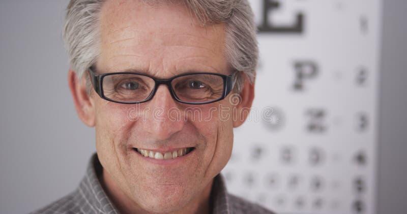 Vidrios masculinos mayores de la prescripción que llevan fotografía de archivo